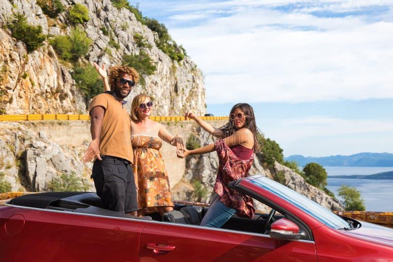 Grupp av lyckligt folk i röd konvertibel bil royaltyfri bild