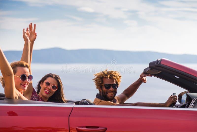 Grupp av lyckligt folk i röd konvertibel bil royaltyfria bilder