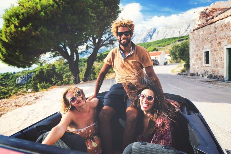 Grupp av lyckligt folk i röd konvertibel bil arkivbilder