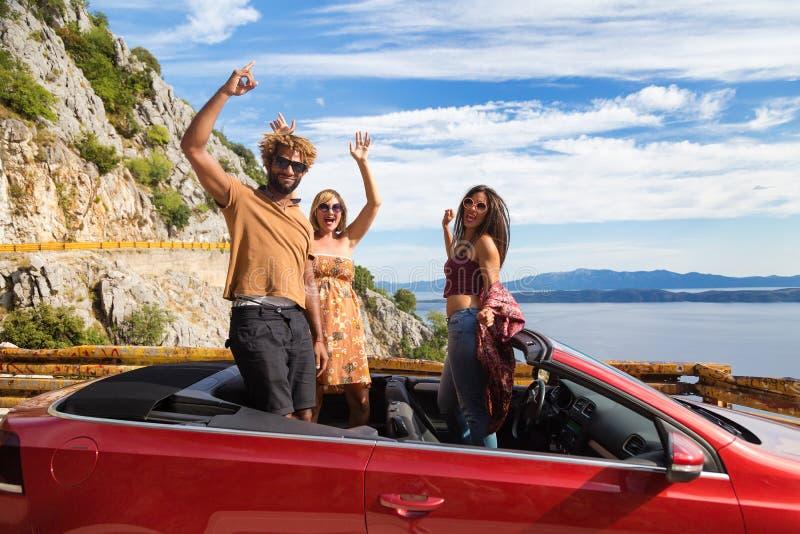 Grupp av lyckligt folk i röd konvertibel bil royaltyfri foto