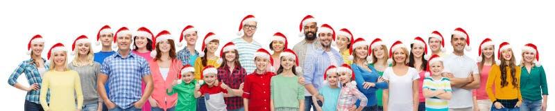 Grupp av lyckligt folk i santa hattar arkivfoton