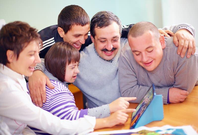 Grupp av lyckligt folk med handikappet som har gyckel med minnestavlan