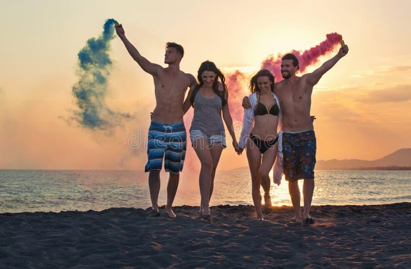Grupp av lyckligt folk som går på den härliga stranden i sommarsolnedgång fotografering för bildbyråer