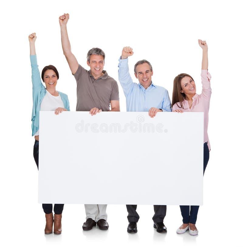 Grupp av lyckligt folk som rymmer plakatet arkivfoto