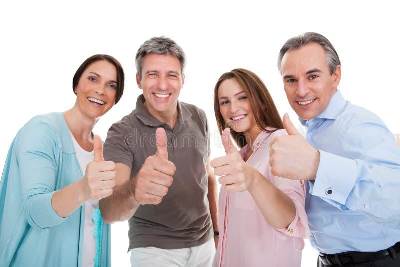 Grupp av lyckligt folk som visar tummen upp tecken arkivfoto