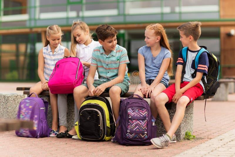 Grupp av lyckligt grundskolastudentsamtal arkivbilder