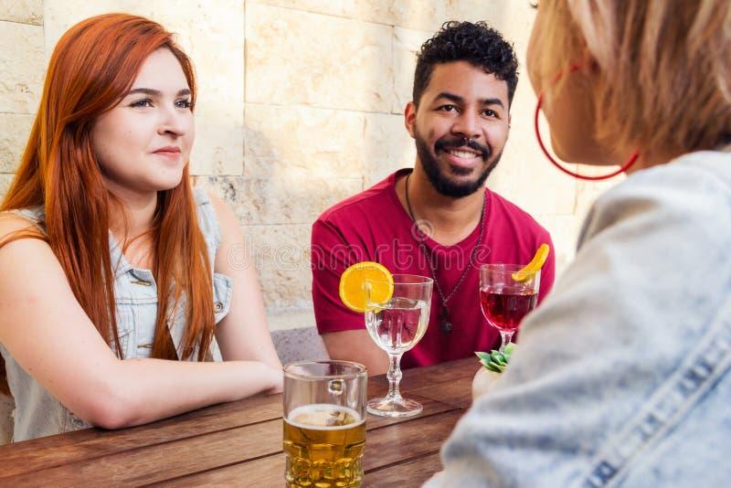 Grupp av lyckligt le folk som umgås i ett parti på restauraen arkivfoto