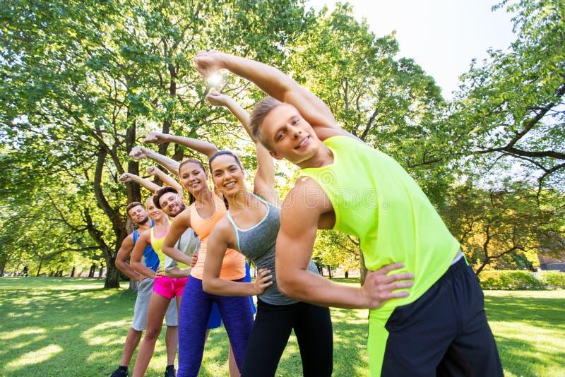 Grupp av lyckligt lottade människor som utövar sin verksamhet i sommarparken royaltyfri fotografi