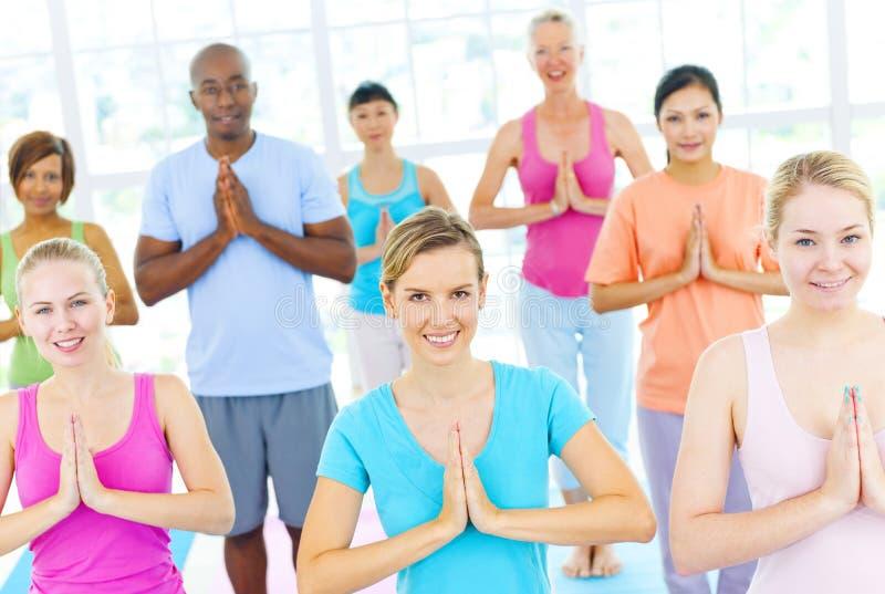 Grupp av lyckligt Mång--person som tillhör en etnisk minoritet folk i en yogagrupp royaltyfri bild