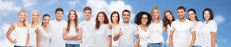 Grupp av lyckligt olikt folk i vita t-skjortor arkivfoto