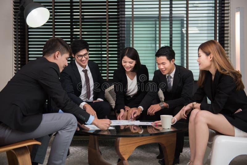 Grupp av lyckligt ungt affärsfolk i möte royaltyfri fotografi