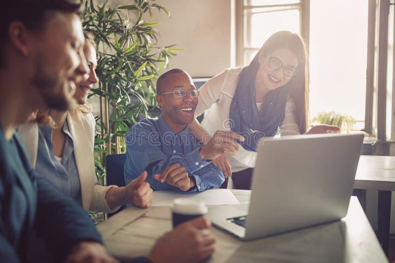 Grupp av lyckligt ungt affärsfolk som använder bärbara datorn, och arbete till arkivfoton