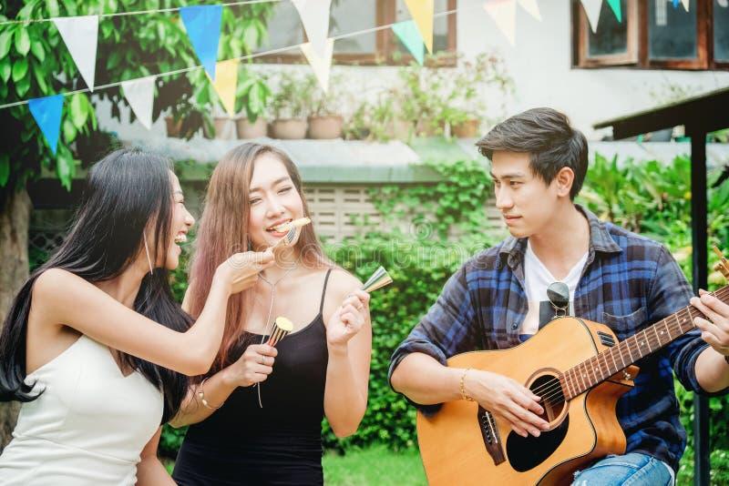 Grupp av lyckligt ungt asiatiskt folk, medan tycka om hem partiet och royaltyfria bilder