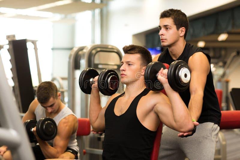 Grupp av män med hantlar i idrottshall arkivfoton