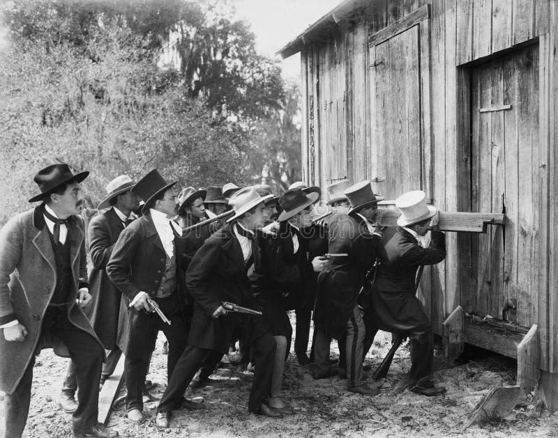 Grupp av män med vapen och bästa hattar som bryter in i en ladugård (alla visade personer inte är längre uppehälle, och inget god royaltyfri fotografi