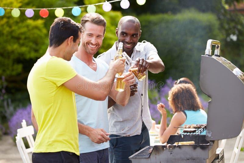 Grupp av män som hemma lagar mat på grillfest royaltyfri foto