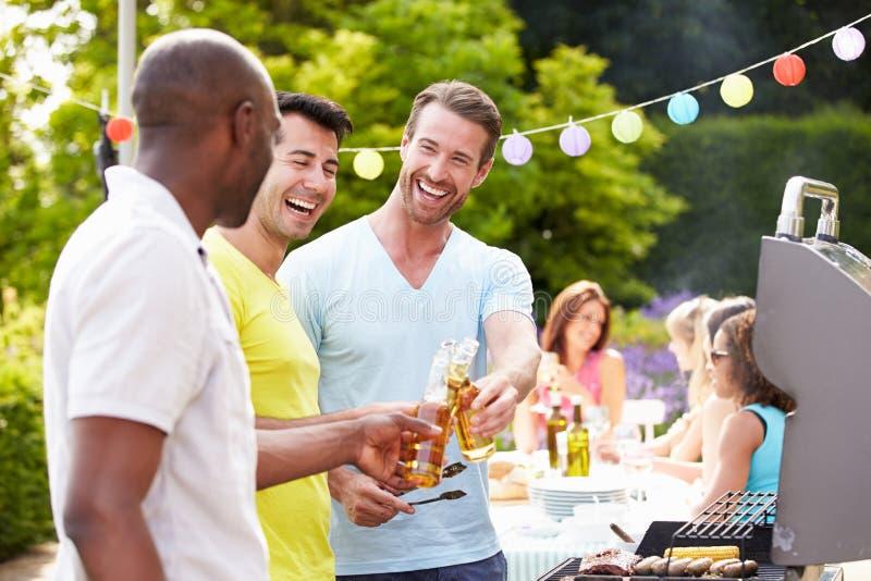 Grupp av män som hemma lagar mat på grillfest royaltyfri bild
