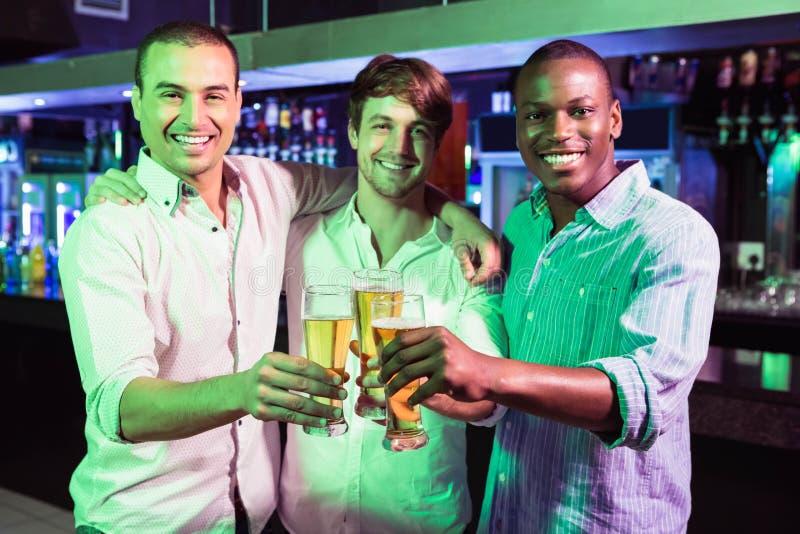 Grupp av män som rostar med exponeringsglas av öl royaltyfri bild