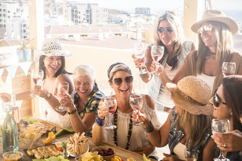 Grupp av människor eller sju kvinnor som tillsammans roar sig och njuter - vänskap till stegar med glas vin - träbord fullt av royaltyfria foton
