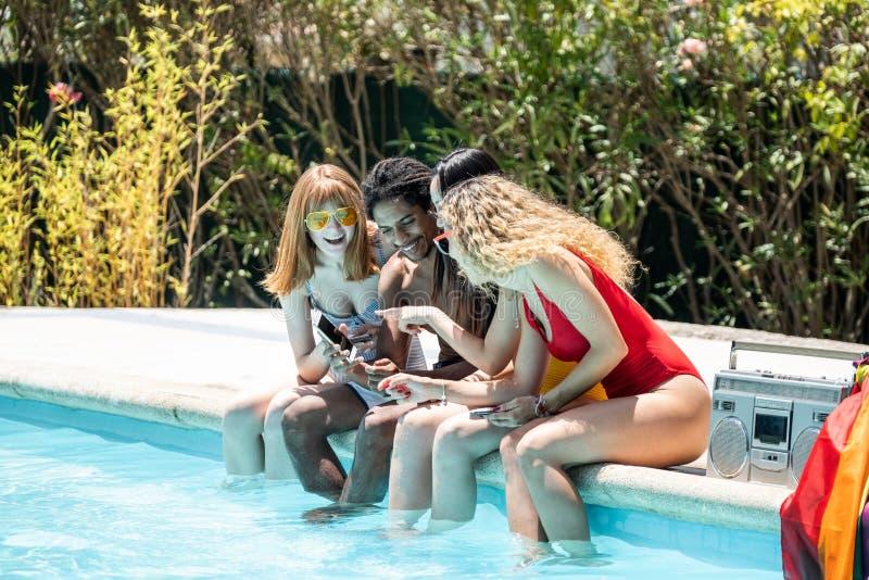 Grupp av människor av olika etnicitet i baddräkter som tittar på mobiltelefonen i utkanten av en pool royaltyfri foto