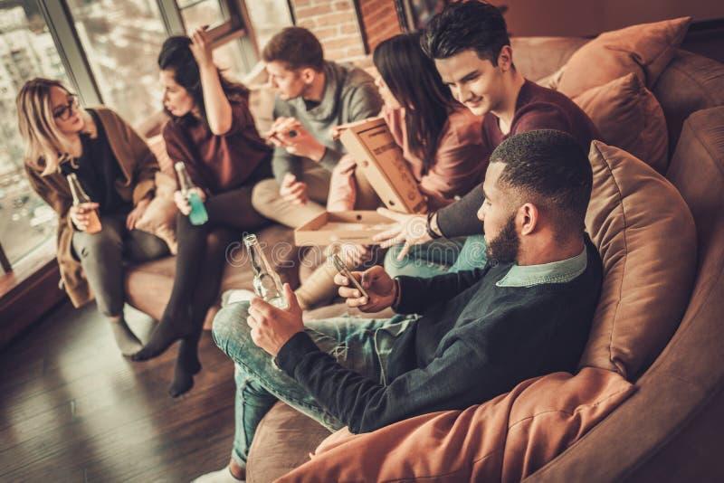 Grupp av mång- etniska unga vänner som äter pizza i hemmiljö royaltyfri foto