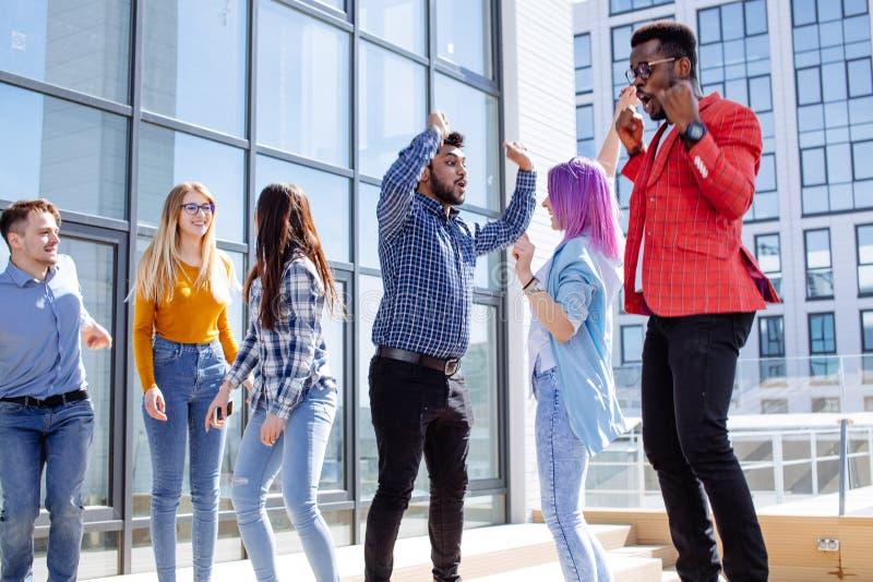 Grupp av mång- etniska ungar som kyler i stads- utomhus- bakgrund royaltyfri foto