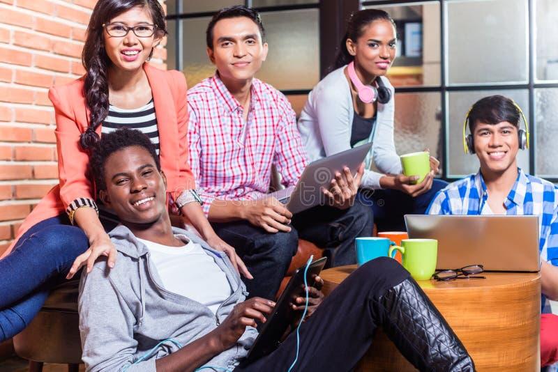 Grupp av mångfaldhögskolestudenter som lär på universitetsområde royaltyfria foton