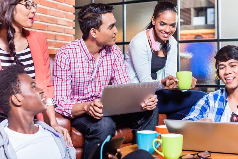 Grupp av mångfaldhögskolestudenter som lär på universitetsområde arkivfoto