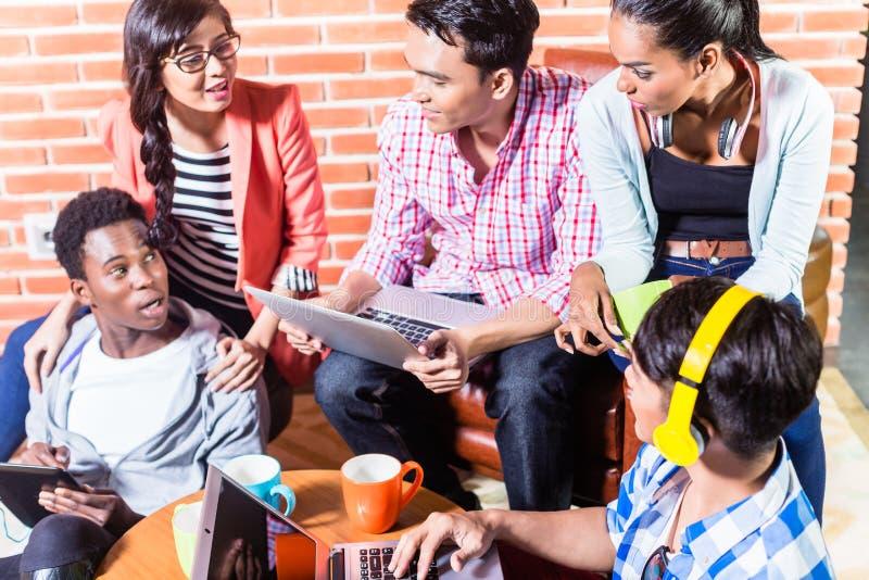 Grupp av mångfaldhögskolestudenter som lär på universitetsområde royaltyfria bilder