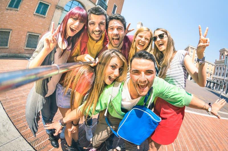Grupp av mångkulturella turistvänner som har gyckel som tar selfie royaltyfri fotografi