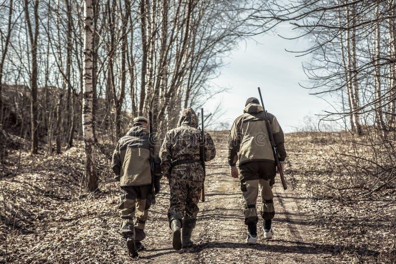 Grupp av manjägare som går upp på den lantliga vägen under jaktsäsong arkivbild