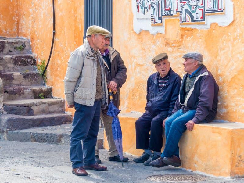 Grupp av manliga äldre Sardinian byar som talar på gatan arkivfoton