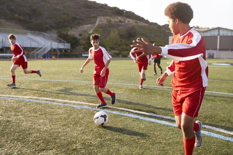 Grupp av manliga högstadiumstudenter som spelar i fotbolllag royaltyfri fotografi