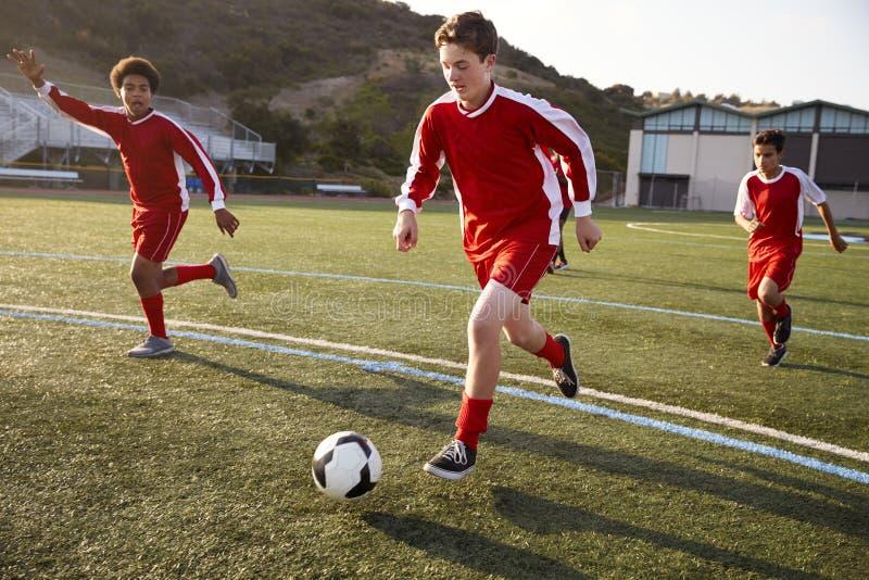 Grupp av manliga högstadiumstudenter som spelar i fotbolllag royaltyfria bilder