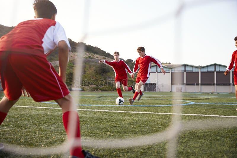 Grupp av manliga högstadiumstudenter som spelar i fotbolllag royaltyfri foto