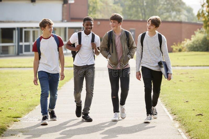 Grupp av manliga tonårs- studenter som går runt om högskolauniversitetsområde royaltyfria bilder