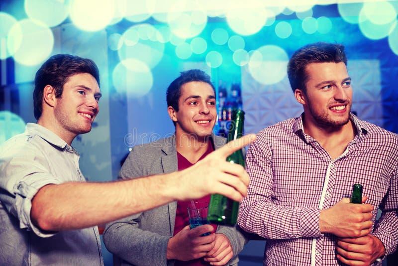 Grupp av manliga vänner med öl i nattklubb royaltyfri fotografi