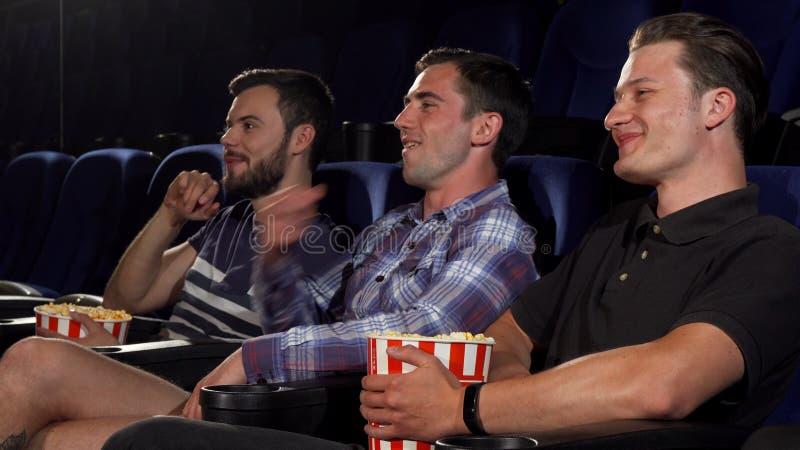 Grupp av manliga vänner som tillsammans håller ögonen på filmer på bion arkivbild