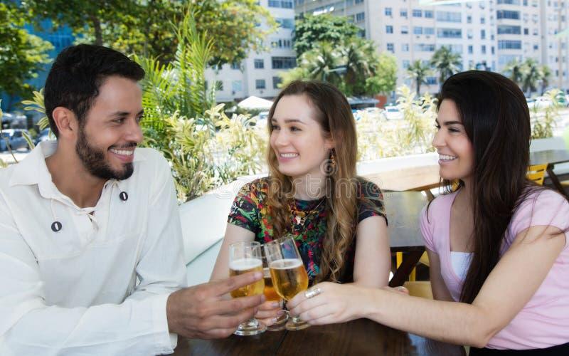 Grupp av mannen och kvinnan som dricker öl i en stång arkivfoton