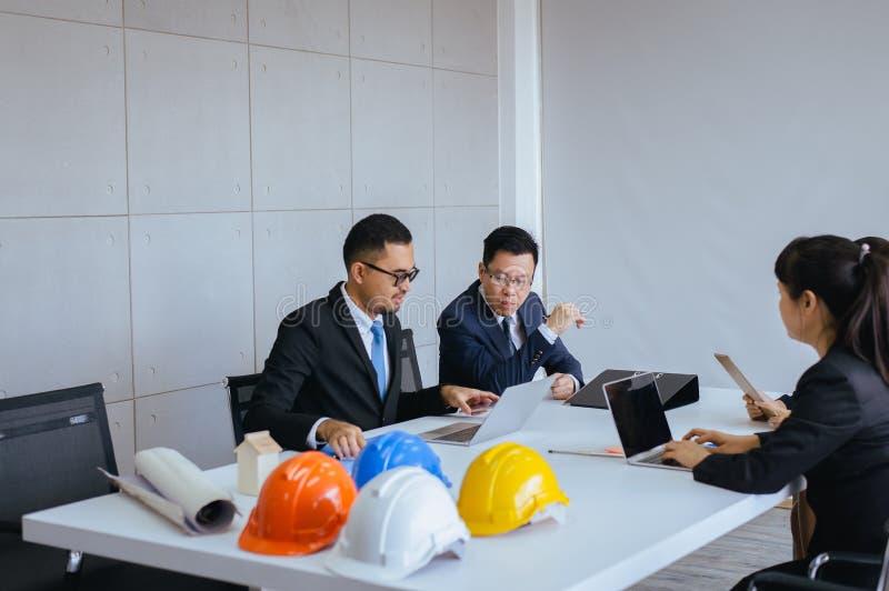 Grupp av meddela för folk för arkitekt asiatiskt mötande och arbetande, medan sitta på rumkontorsskrivbordet tillsammans royaltyfri fotografi