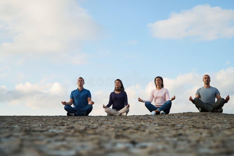 Grupp av meditation och yoga för fyra personer praktiserande arkivfoton