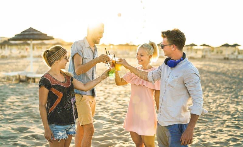 Grupp av millennial lyckliga vänner ha gyckel på strandpartiet som dricker utsmyckade coctailar på solnedgången - sommarglädje oc arkivfoto