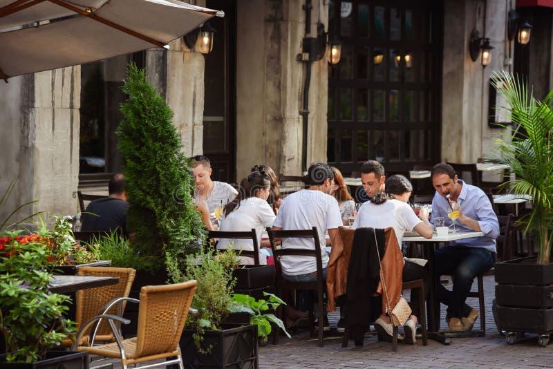 Grupp av millennials som utanför äter matställen på den exklusiva restaurangen royaltyfri foto