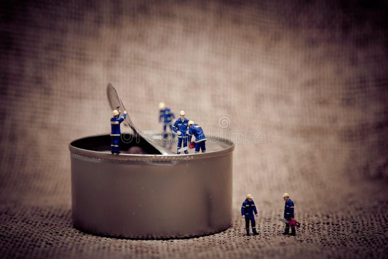 Grupp av miniatyrarbetare som öppnar en can Stämd makro för färgsignal arkivfoto