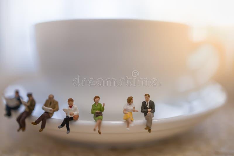Grupp av miniatyrfolkdiagram som sitter, talar, väntar och läser tidningen och boken på den vita plattan av koppen av varmt kaffe royaltyfri foto