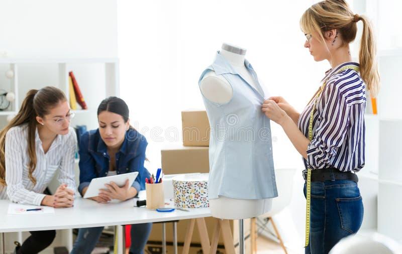 Grupp av modeformgivare som arbetar och avgör detaljer av den nya samlingen av kläder i systugan royaltyfri fotografi