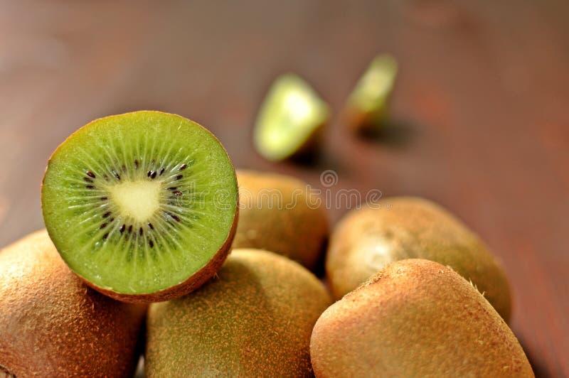 Grupp av mogen hel kiwi och halv kiwi på brun träbakgrund royaltyfria foton