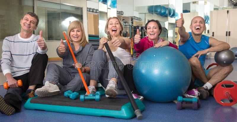 Grupp av moget folk som poserar med gymnastiska lättheter på Get royaltyfria foton