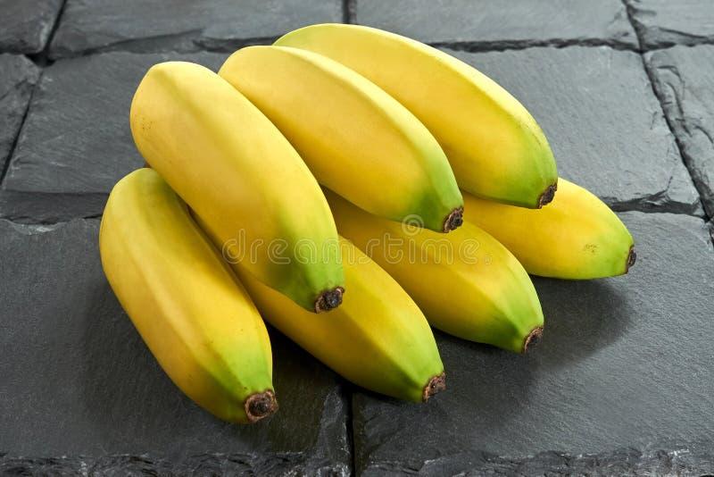 Grupp av mogna bananer på en svart bakgrundsskiffersten royaltyfri fotografi