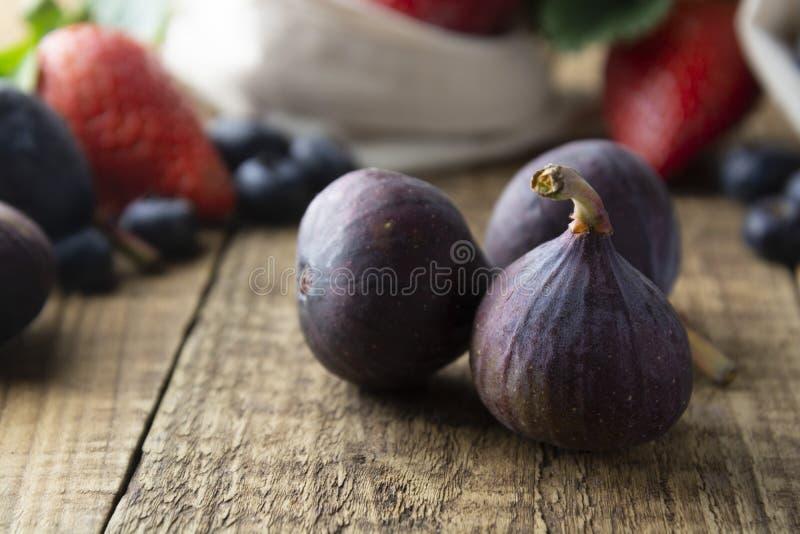 Grupp av mogna fikonträd på den lantliga trätabellen Nya figs på den lantliga trätabellen Bio frukter för frukost eller efterrätt royaltyfri foto